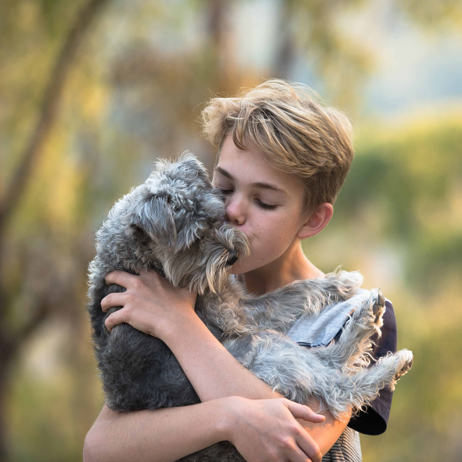 Niño besando y abrazando a un perro